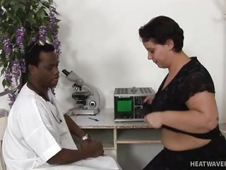 black doctor examines woman's big boobs