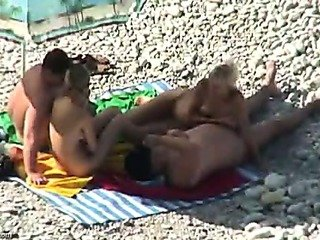 2 tanned couples have relaxation on a beach
